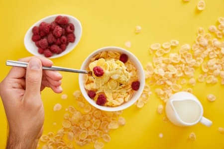 Photo for Cropped view of man holding spoon above  bowl with cornflakes, fresh raspberry and jug of milk isolated on yellow - Royalty Free Image