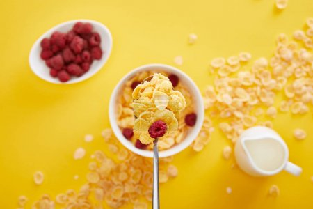 Photo for Top view of spoon with cornflakes and fresh raspberry above bowl with breakfast isolated on yellow - Royalty Free Image