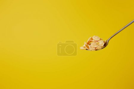 Photo for Spoon with sweet cornflakes isolated on yellow - Royalty Free Image