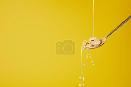Photo for Spoon with cornflakes and milk stream isolated on yellow - Royalty Free Image