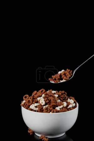 Photo for White bowl with assorted cereal and spoon isolated on black - Royalty Free Image