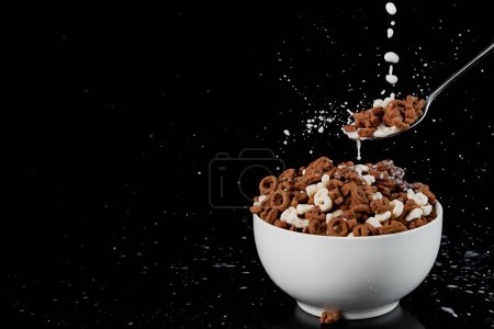 Photo for White bowl with assorted cereal and spoon with milk drops isolated on black - Royalty Free Image