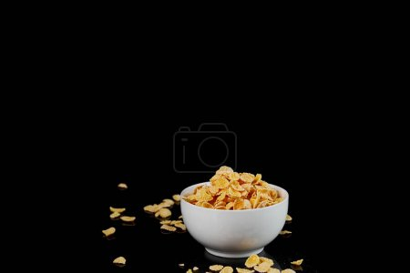 Photo for White bowl with cornflakes and scattered pieces isolated on black - Royalty Free Image