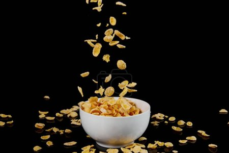 Photo for White bowl with cornflakes and fallen pieces isolated on black - Royalty Free Image