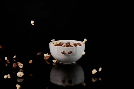 Photo for White bowl with cereal and fallen pieces isolated on black - Royalty Free Image