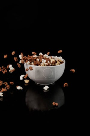 Photo for White bowl with cereal and dropped pieces isolated on black - Royalty Free Image