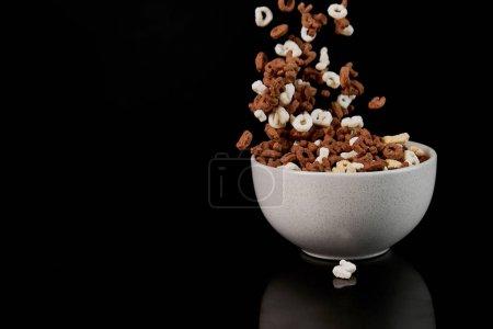 Photo pour Bol blanc avec les morceaux tombés de céréales d'isolement sur le noir - image libre de droit