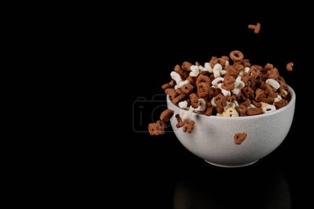 Photo for White bowl with cereal and scattered pieces isolated on black - Royalty Free Image