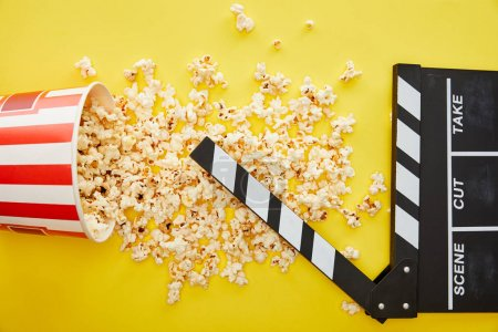 Photo for Top view of delicious popcorn scattered on yellow background with clapper board - Royalty Free Image