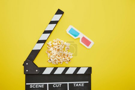 Photo for Top view of crunchy popcorn near clapper board and 3d glasses on yellow background - Royalty Free Image