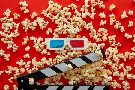 Photo for Top view of delicious popcorn scattered on red background near clapper board and 3d glasses - Royalty Free Image