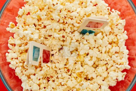 Photo for Top view of delicious popcorn in glass bowl with 3d glasses - Royalty Free Image