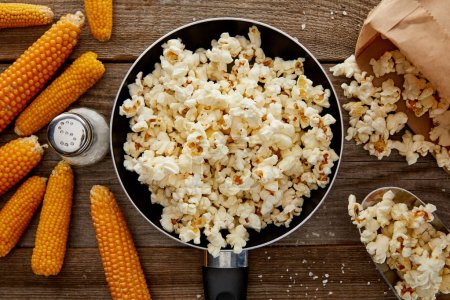 Photo for Top view of salty popcorn in frying pan near corn on wooden background - Royalty Free Image