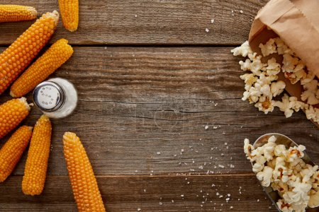 Photo for Top view of delicious popcorn and corn with salt on wooden background - Royalty Free Image