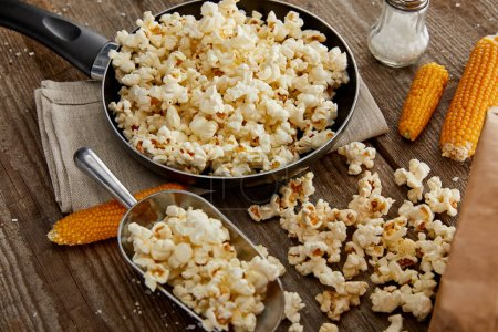 Photo for Delicious popcorn in frying pan and on wooden table - Royalty Free Image