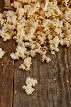 Photo for Delicious popcorn scattered on wooden background - Royalty Free Image