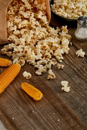 Photo for Delicious popcorn scattered from paper bag near corn and frying pan on wooden background - Royalty Free Image