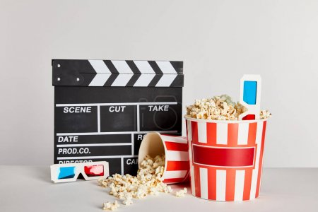 delicious popcorn scattered from buckets with clapper board and 3d glasses isolated on grey