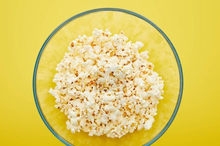 Photo for Top view of delicious popcorn in glass bowl on yellow background - Royalty Free Image