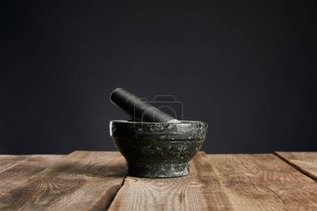 Photo for Grey stone mortar on wooden table isolated on black - Royalty Free Image
