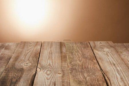 Foto de Mesa de madera vacía sobre fondo marrón con linterna - Imagen libre de derechos