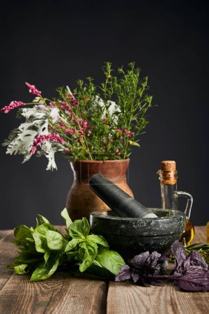 grey mortar, clay vase with herbs and bottle on wooden table isolated on black