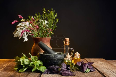 Photo for Grey mortar near clay vase with fresh wildflowers and herbs on wooden table isolated on black - Royalty Free Image