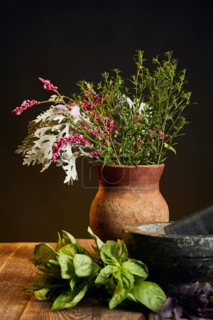 Photo for Clay vase with fresh wildflowers and herbs on wooden table isolated on black - Royalty Free Image