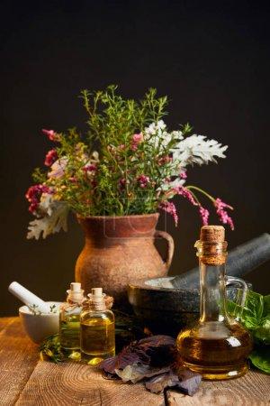 Photo pour Vase en argile avec des herbes et des fleurs fraîches près de mortier et pilon et bouteilles sur table en bois - image libre de droit