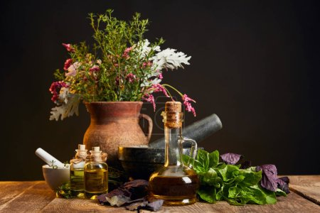 Photo for Clay vase with fresh herbs and flowers near mortar and pestle and bottles on wooden table isolated on black - Royalty Free Image