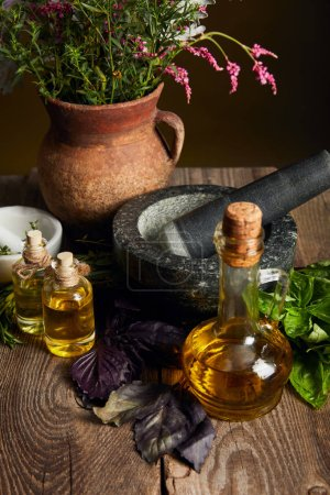 Photo for Mortar with pestle, bottles with oil and clay vase with fresh wildflowers on wooden surface isolated on black - Royalty Free Image