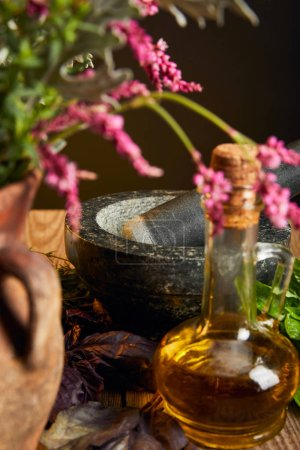 mortar with pestle near bottle with oil and vase with fresh wildflowers on wooden surface isolated on black