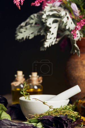 Photo for White mortar with pestle near bottles and vase with fresh flowers on wooden surface isolated on black - Royalty Free Image