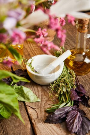 Mörser mit Stößel in Flaschennähe und frischen Blättern und Blüten auf Holzoberfläche