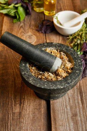 Photo pour Mortiers avec pilons avec mélange à base de plantes sur surface en bois - image libre de droit