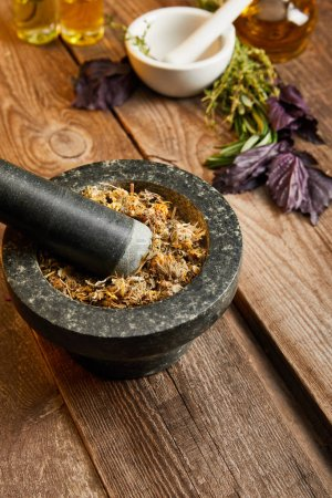 Photo for Mortars with pestles with herbal mix near fresh basil on wooden surface - Royalty Free Image