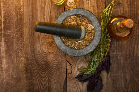 Photo for Top view of mortar with pestle near fresh herbs and bottles on wooden surface with copy space - Royalty Free Image