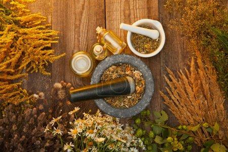 Foto de Vista superior de morteros y botellas cerca de flores silvestres y hierbas en la superficie de madera - Imagen libre de derechos