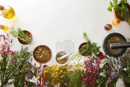 Photo for Top view of mortars and pestles with herbal blends near flowers on white background - Royalty Free Image