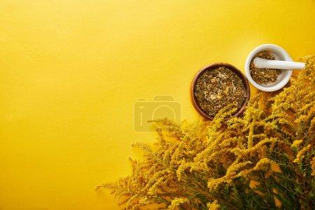 Foto de Vista superior de morteros con mezcla de hierbas cerca de racimos goldenrod sobre fondo amarillo - Imagen libre de derechos