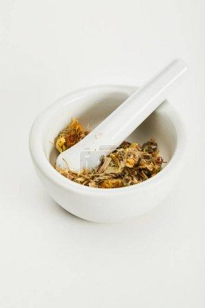 Foto de Mortero y pestle con mezcla de té de hierbas sobre fondo blanco - Imagen libre de derechos