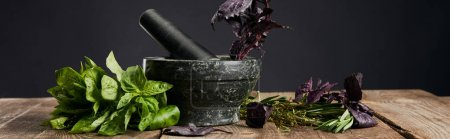 Photo for Panoramic shot of mortar and pestle with basil on wooden table isolated on black - Royalty Free Image