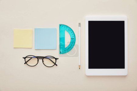 top view of sticky notes near glasses and digital tablet with blank screen isolated on beige