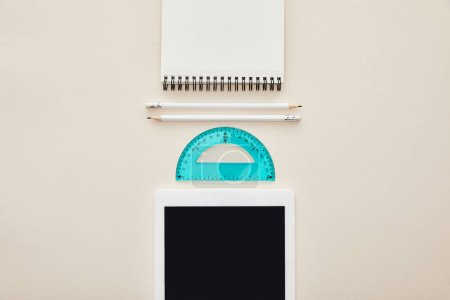 Draufsicht auf Bleistifte, Notizbuch und Lineal in der Nähe digitaler Tablets mit leerem Bildschirm isoliert auf beige