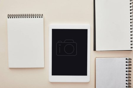 Photo pour Notebooks near digital tablet with blank screen isolated on beige - image libre de droit