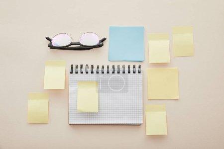 Photo pour Vue du haut des notes autocollantes vierges sur carnet près des lunettes isolées sur beige - image libre de droit