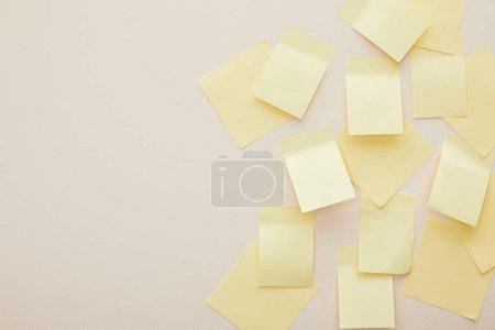Photo pour Vue de dessus des notes collantes jaunes isolées sur beige - image libre de droit