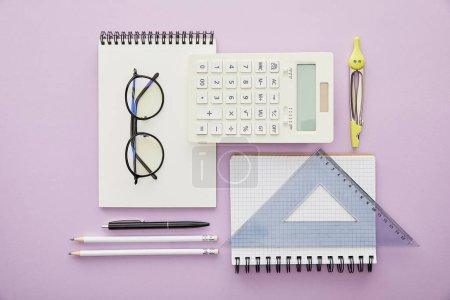 Photo pour Couché plat avec des règles et une calculatrice près des ordinateurs portables et de la papeterie isolés sur violet - image libre de droit