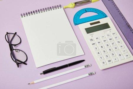 Foto de Los gobernantes y la calculadora cerca del cuaderno y las gafas aisladas en púrpura - Imagen libre de derechos