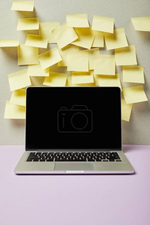 Photo for Laptop with blank screen near empty sticky notes on grey and purple - Royalty Free Image